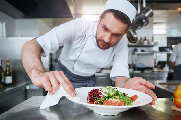 Еда - наша религия, готовит блюдо для сервировки.