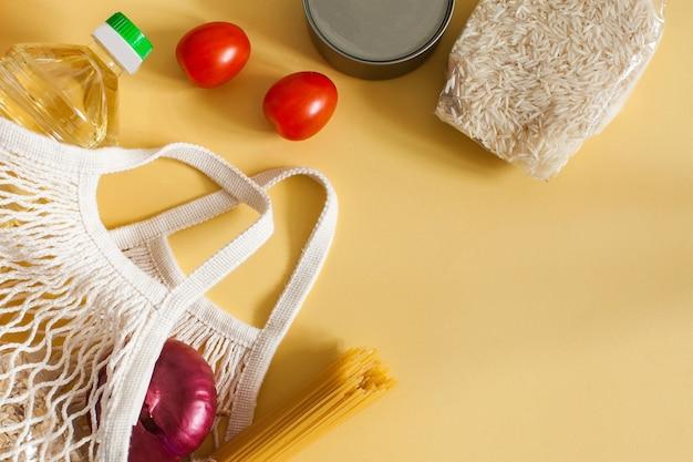 テキスト用のスペースがある黄色い表面のストリングバッグに入った食品