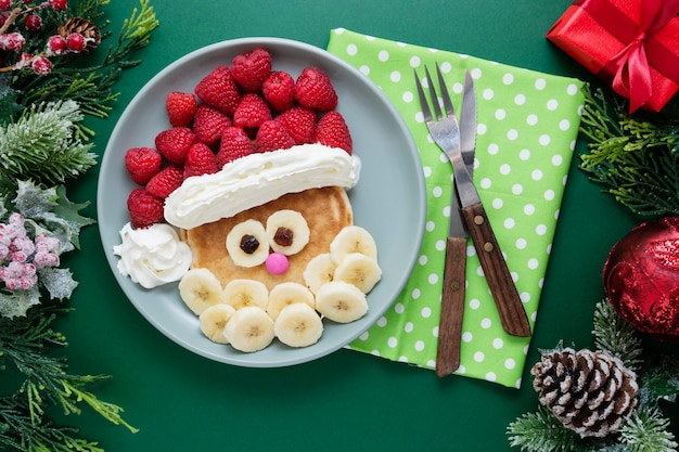 Food for kids. christmas santa pancake with fruits for children.