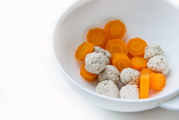 Food for kids, first lure for babies, pieces of carrot and turkey in a plate