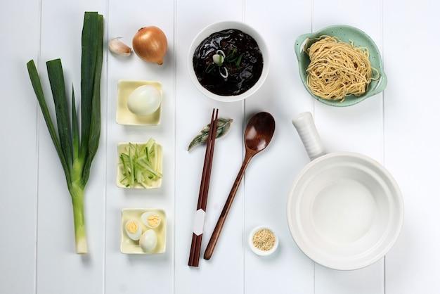 Food knolling asian noodle, flat lay concept ingredients of jajangmyeon или jjajangmyeon, корейская лапша с соусом из черной фасоли. на белом деревянном фоне
