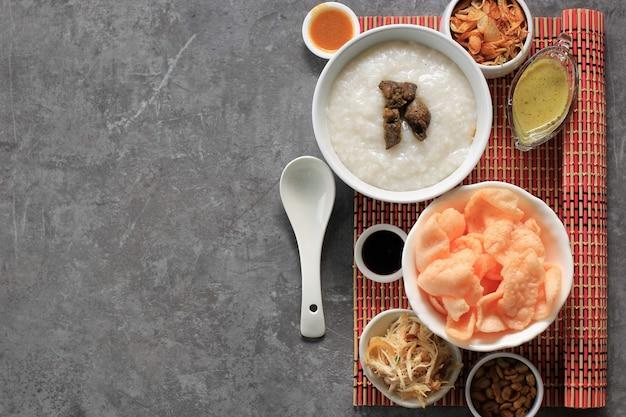 음식 knolling bubur ayam 또는 갈가리 찢긴 닭고기를 곁들인 인도네시아 쌀 죽. kerukpuk(크래커), 간장, 튀긴 콩, 삼발과 함께 제공됩니다. 복사 공간
