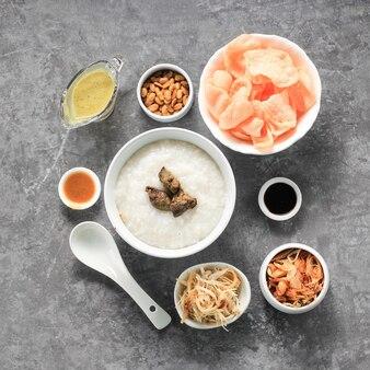 음식 knolling bubur ayam 또는 갈가리 찢긴 닭고기를 곁들인 인도네시아 쌀 죽. kerukpuk(크래커), 간장, 튀긴 콩, 삼발과 함께 제공됩니다.