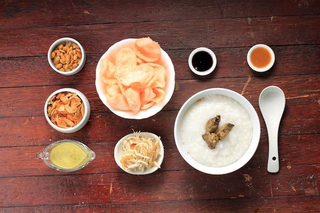 Food knolling concept bubur ayam 또는 갈가리 찢긴 닭고기를 곁들인 인도네시아 쌀 죽. kerukpuk (크래커), 간장, 튀긴 콩, 삼발과 함께 제공