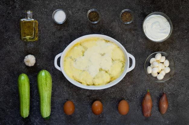 フードノリング。若いズッキーニをにんにくソースでオーブン焼き。暗いテーブルの上の白い皿の周りの材料のレイアウト。