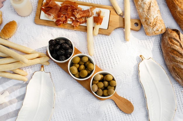 Food lay out on picnic blanket. fresh baked bread, olives and photocam lay on white blanket