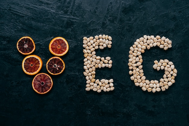 Food letters. garbanzo and slice of citrus fruit in form of veg letters on dark background.