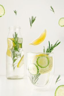 Food levitation concept. detox water or lemonade with lemon, cucumber and rosemary in a glass. weight loss and healthy lifestyle.