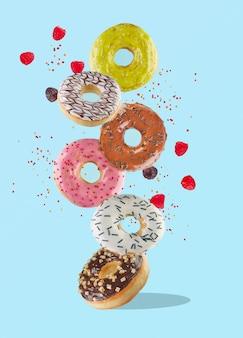 食べ物の浮揚-ラズベリーと色付きのスプリンクルで空を飛んでいる甘いカラフルなドーナツ。