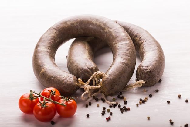 食べ物、肉、そしておいしいコンセプト-馬の肉とトマトをテーブルに置いて作ったソーセージ。
