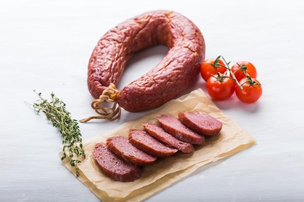 食べ物、肉、おいしいコンセプト-馬の肉とトマトをテーブルに置いて作ったソーセージ