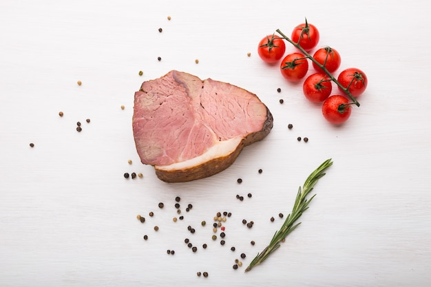 Food, meat and delicious concept - horse meat with pepper and tomatoes, top view