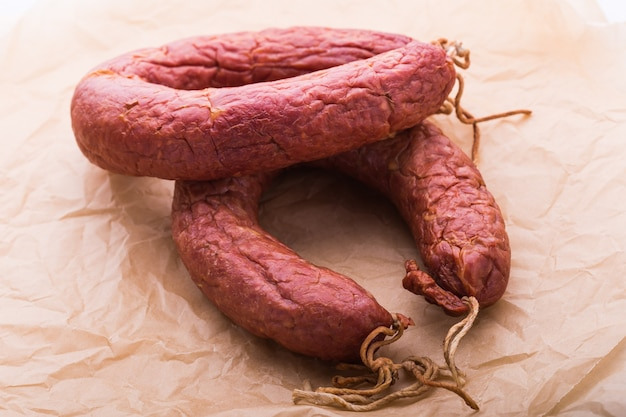 Food, meat and delicious concept - sausages made with horse meat with tomatoes on table