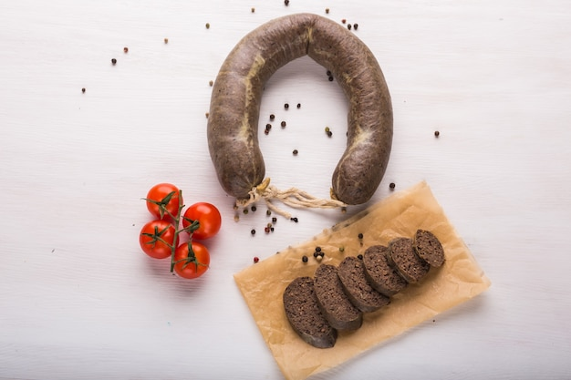 Food, meat and delicious concept - sausages made with horse meat with tomatoes on table.