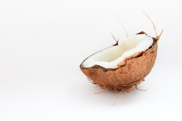 Еда, минимализм, цвет, натюрморт и естественная концепция - половина кокоса крупным планом на белом фоне