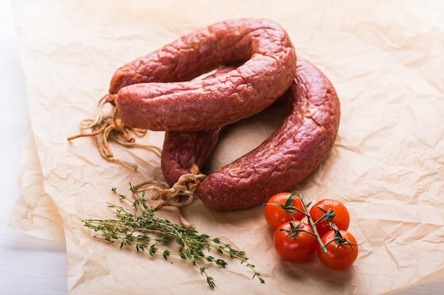 Еда, национальная кухня и вкусная концепция - закройте традиционные казахские колбасы из конины с помидорами и тмином.