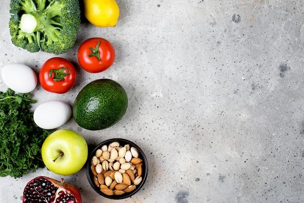 食品栄養コンセプト。軽い石のテーブル背景に野菜、果物、豆製品。トップビュー、フラットレイアウト、コピースペース