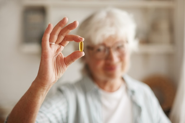 Food, nutrition, diet and health concept. close up shot of elderly woman's hand holding fish oil or omega-3 polyunsaturated fatty acid supplement in shape of capsule, going to take one during lunch