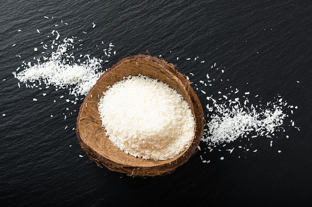 Food organic dried desiccated coconut in the coconut shell with copy space