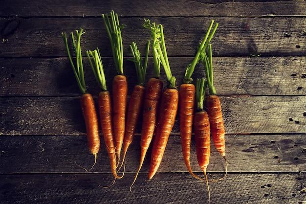 음식 유기농 야채 화려한 배경입니다. 나무 테이블에 맛있는 신선한 당근. 복사 공간이있는 상위 뷰. 건강한 생활 개념.