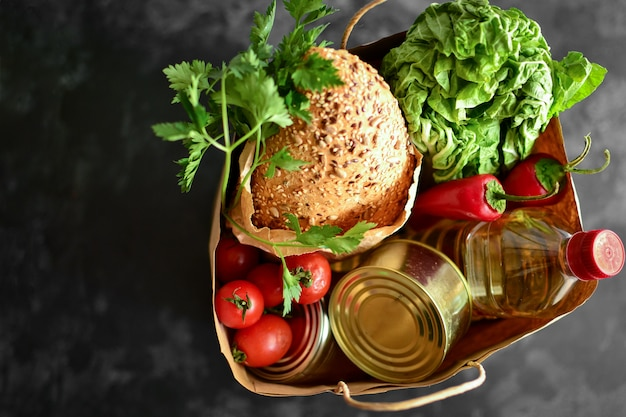 Food in a paper bag. food donation or food delivery concept. . oil, bread, cabbage, salad, vegetables, canned food. top view.