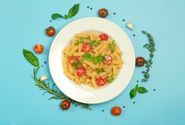 Food pasta on a blue background. italian fusilli pasta with tomatoes, herbs and basil on a white plate
