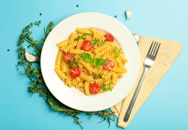 Food pasta on a blue background. italian fusilli pasta with tomatoes, herbs and basil on a white plate.