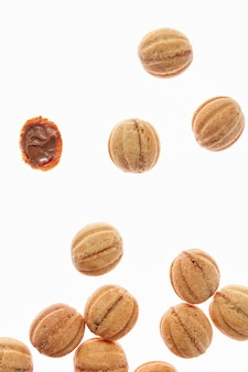Food pattern with freshly baked homemade cakes in a shape of walnuts filled a condensed milk cream on a white background, copy space.