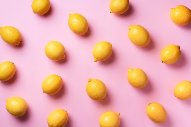 Food pattern with lemons on pink paper background