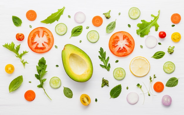 Food pattern with raw ingredients of salad on white wooden background.