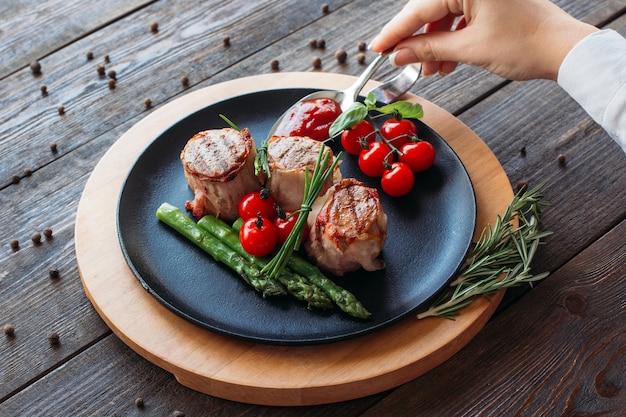 食べ物の写真。豚肉料理を飾る女性