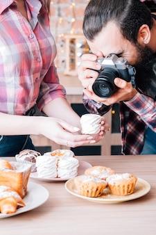 직장에서 음식 사진 작가 및 조수. 머랭의 남자와 여자 복용 사진입니다. 주위에 케이크와 파이 구색.