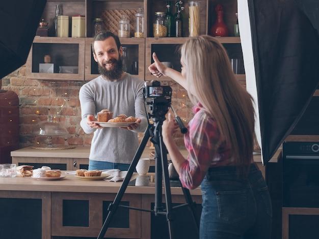 직장에서 음식 사진 작가. 백 스테이지 사진. 신선한 파이 구색 웃는 남자를 촬영 여자 엄지.