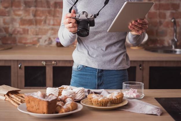 음식 사진 작가. 블로깅 사업. 태블릿 및 카메라를 가진 남자입니다. 주위에 케이크와 파이 구색.