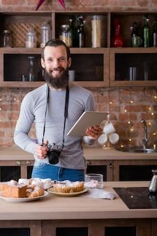 음식 사진 작가. 블로깅 사업. 태블릿 및 카메라 웃는 남자. 주위에 케이크와 파이 구색.