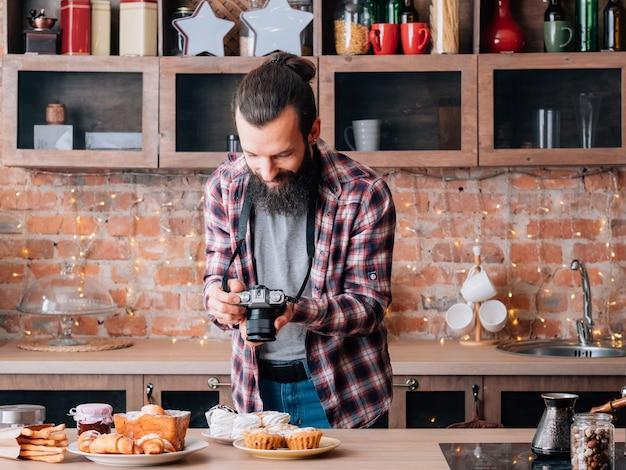 음식 사진 작가. 디저트 구색. 신선한 홈 메이드 패스트리의 사진을 찍는 카메라를 가진 남자