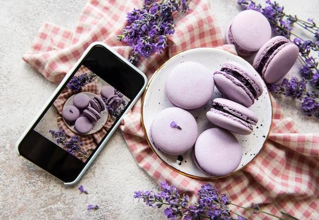음식 사진 개념입니다. 스마트폰으로 찍은 라벤더와 프랑스 디저트 마카롱 사진