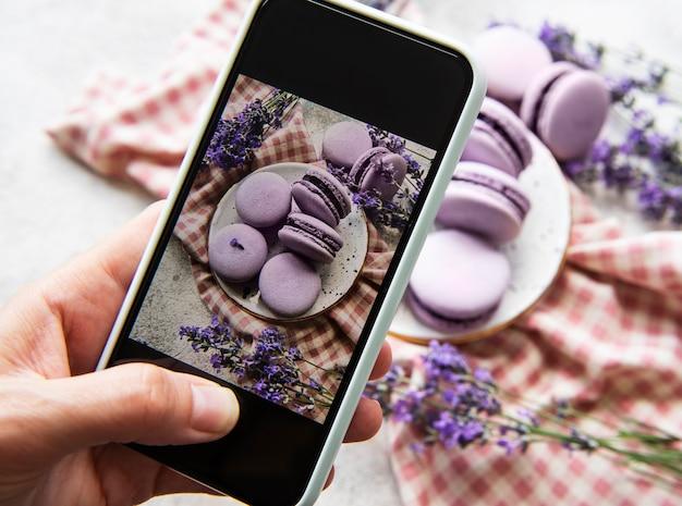 フードフォトグラフィーのコンセプト。スマートフォンで撮影したラベンダーとフランスのデザートマカロンの写真