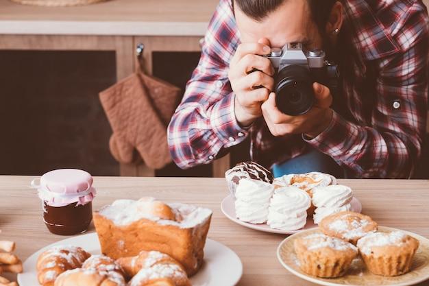 음식 사진. 수제 달콤한 빵집. 신선한 파이의 사진을 찍고 카메라를 가진 남자.