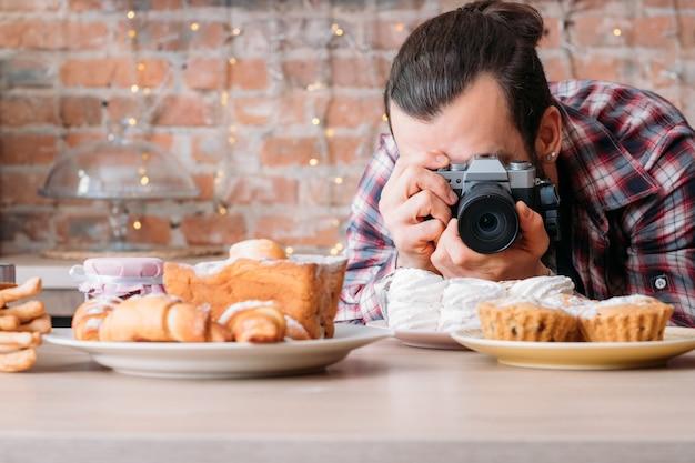 음식 사진. 과자 디저트 구색. 머랭으로 접시의 사진을 찍고 카메라를 가진 남자