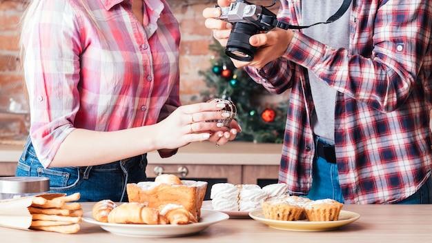 음식 사진. 팀워크. 신선한 수제 케이크와 패스트리의 사진을 찍는 여자 도우미와 남자.