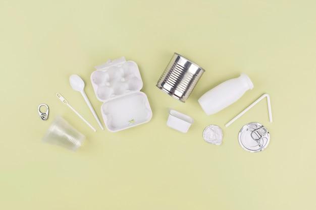 緑の背景に食品プラスチック、金属、段ボール包装。プラスチックとエコロジーのリサイクルの概念。プラスチック廃棄物。