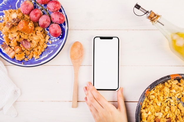 Food plates and hand with mobile phone on cooking table