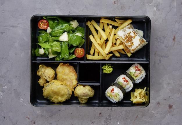 Порция еды в японской бенто коробке с суши роллами и салатом