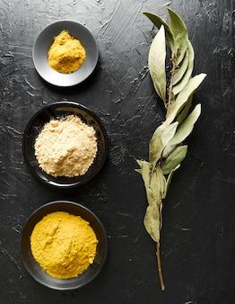 Food powder in bowls and ingredient leaves