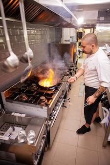 食品の調理。シェフは、フライパンで大火を使って調理するクレイジーなシェフ。