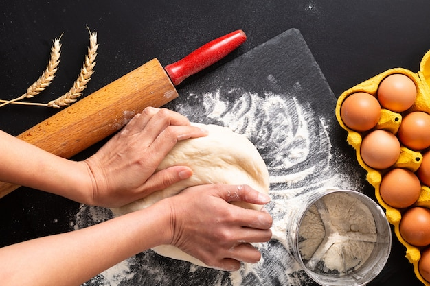 Food preparation concept over head shot kneading dough for bakery, pizza or pasta on black background with copy space