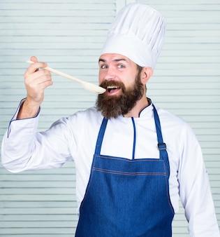食品の調理。ベジタリアン。あごひげを生やした成熟したシェフ。ダイエットと有機食品、ビタミン。ひげを生やした男がキッチンで料理をします。帽子をかぶったシェフの男。秘密の味のレシピ。健康的な料理。
