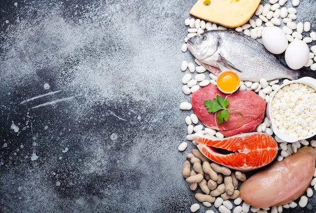 バランスの取れたケトン体生成低炭水化物ダイエットのための食品:魚、肉、鶏肉、卵、乳製品、豆、チーズ、ナッツ。灰色の背景。ダイエットと体重減少のためのケト製品のコンセプト、上面図、テキスト用のスペース