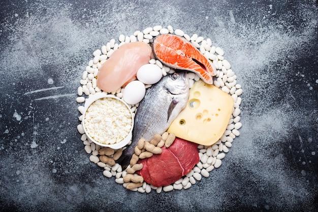 バランスの取れたケトジェニック低炭水化物ダイエットのための食品:魚、肉、鶏肉、卵、乳製品、豆、チーズ、灰色の背景のナッツ。ダイエットと体重減少のためのケト製品のコンセプト、上面図、クローズアップ